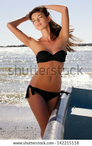 Beautiful woman enjoying her time on the beach on a sunny perfect day, sexy woman in swimsuit getting a tan - stock photo