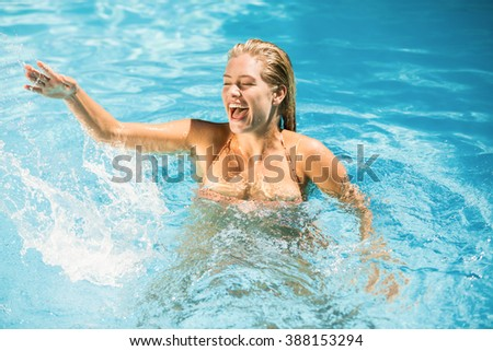 Beautiful woman enjoying in swimming pool on a sunny day