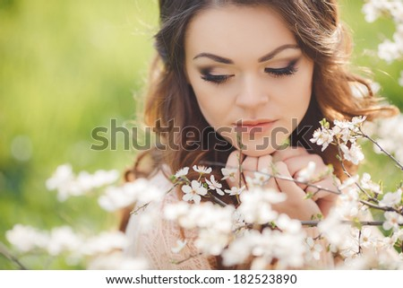 Beautiful woman enjoying outdoors, nice female. pretty girl relaxing outdoor, having fun,  happy young lady and spring green nature and blooming trees, harmony concept - stock photo