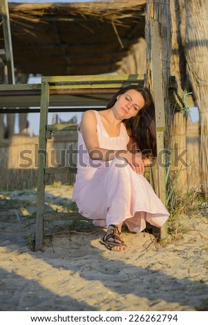 Beautiful woman enjoying summer vacation on the beach on sunset. Portrait of a beautiful young woman on the beach. - stock photo
