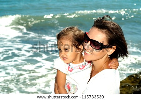 Beautiful woman enjoying the sea breeze with her daughter - stock photo
