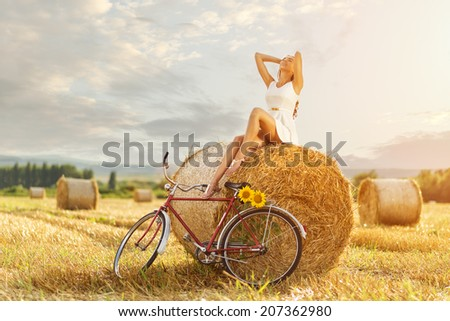 Beautiful woman enjoying the sun in a straw bale, next to the old red bicycle - stock photo
