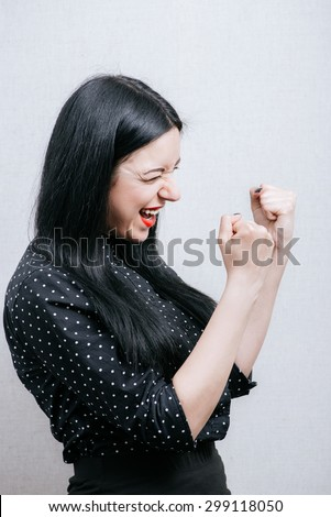 Beautiful Woman enjoys victory. On a gray background.