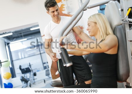 Beautiful woman exercising in gym with some help by personal trainer - stock photo