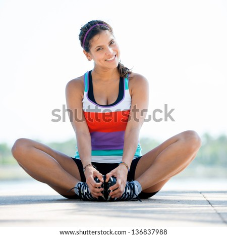 Beautiful woman exercising outdoors and looking very happy - stock photo