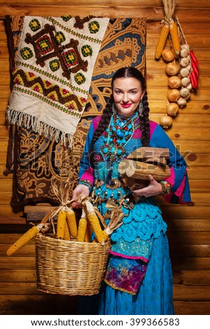 beautiful woman extravagant costume east asia, village, rustic decor, bright clothes with an armful of firewood