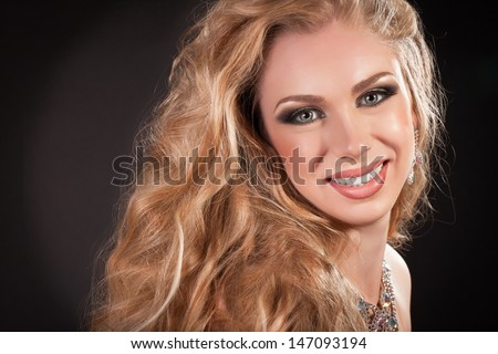 Beautiful Woman Face blonde Hair beauty and jewelry Model . Perfect Skin Professional Make-up. Beauty spa concept skincare. Attractive smiling woman with bright makeup curly blonde hair. Perfect smile