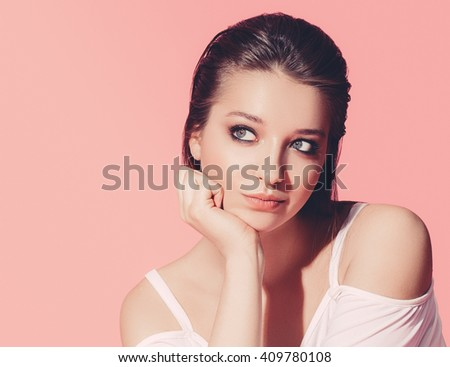 Beautiful woman face close up portrait young studio on pink background  - stock photo