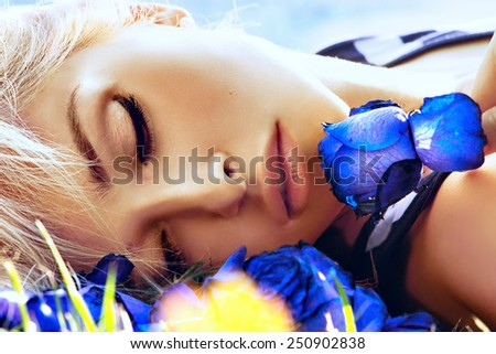 Beautiful woman face closeup. Soft portrait with blue roses - stock photo