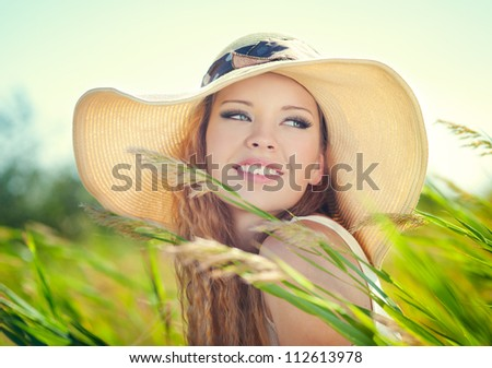 Beautiful woman face on summer meadow - stock photo