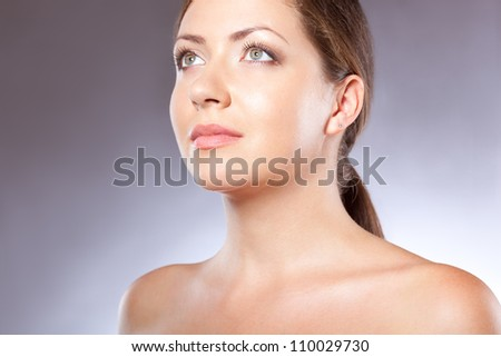 beautiful woman face portrait looking up over blue - stock photo