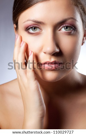 beautiful woman face portrait with hand over blue looking at camera
