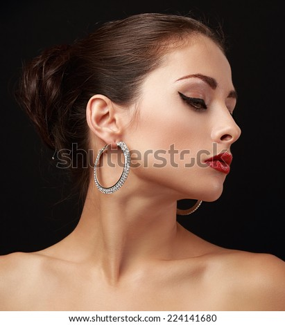 Beautiful woman face profile in fashion earrings with elegant hairstyle on dark black background - stock photo