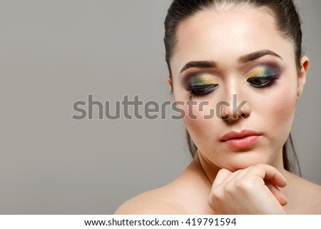 Beautiful woman face with bright makeup close up in studio