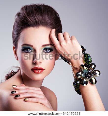 Beautiful woman face with fashion green make-up and jewelry on hand - stock photo