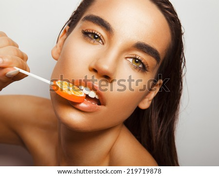 Beautiful woman face with lollipop on her lips. Toned in warm colors, studio shot, horizontal. - stock photo