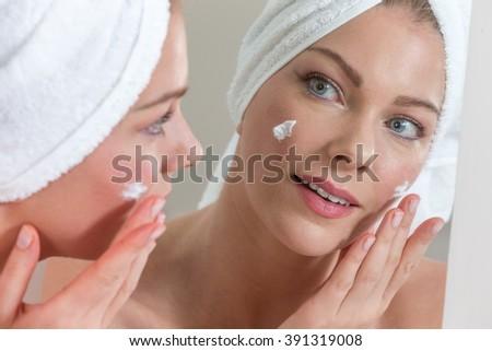 Beautiful woman face with moisturising cream.   - stock photo