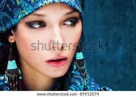 beautiful woman face with oriental scarf around, studio shot - stock photo