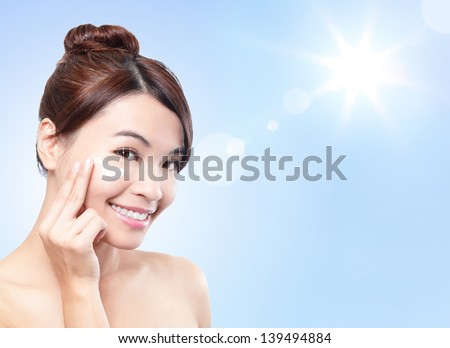 Beautiful woman face with sunshine and blue sky, concept for summer skin care and sun block, asian beauty - stock photo