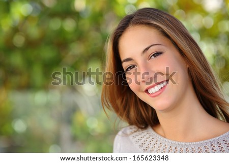 Beautiful woman facial with a perfect white smile outdoor with a green background               - stock photo