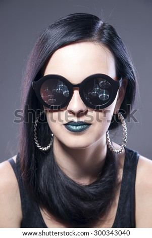 Beautiful woman fashion model portrait in sunglasses with blue lips and earrings. Creative hairstyle and make up. Beauty girl on a gray background - stock photo