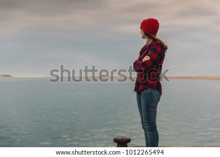 Beautiful woman felling cold near the lake