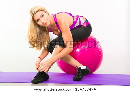 beautiful woman fitness instructor sitting on stability ball in gym