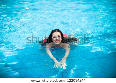 Beautiful woman floating in a swimming pool. - stock photo