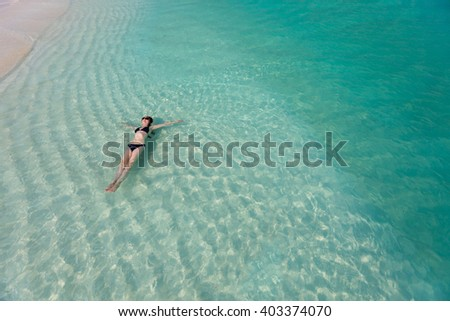 Beautiful woman floating in turquoise tropical water - stock photo