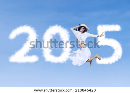Beautiful woman flying on the sky with cloud shaped number 2015 - stock photo