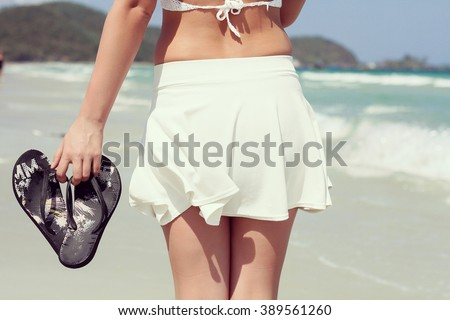 beautiful woman from behind on summer vacations in a tropical beach holding shoes