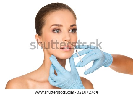 Beautiful woman gets an injection in her face isolated on white - stock photo