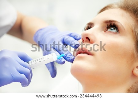 Beautiful woman gets an injection in her lips