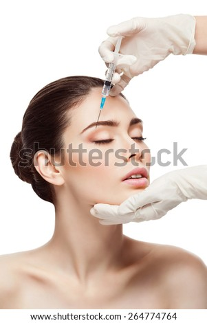 Beautiful woman gets injection in her face. Isolated over white background - stock photo