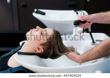 Beautiful woman getting a hair wash in beauty salon - stock photo