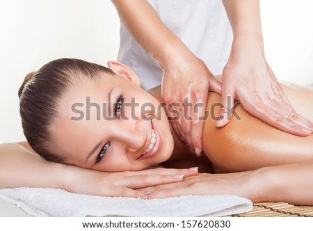 Beautiful woman getting a massage on a white background - stock photo