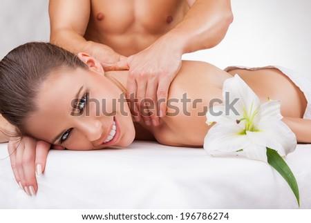 Beautiful woman getting a massage on a white background - stock photo