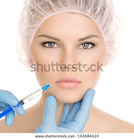 Beautiful woman getting cosmetic injection in lips, isolated over white background. Nice attractive blonde model in medical cap. - stock photo