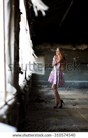 Beautiful woman, girl posing in abandoned house - stock photo