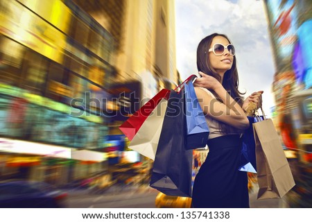 beautiful woman goes shopping in the city - stock photo
