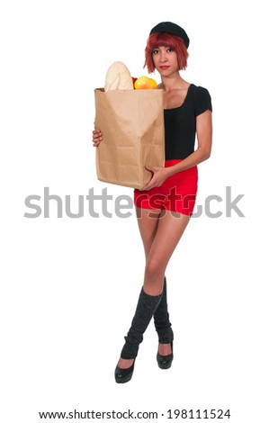 Beautiful woman grocery shopping holding a brown paper bag - stock photo