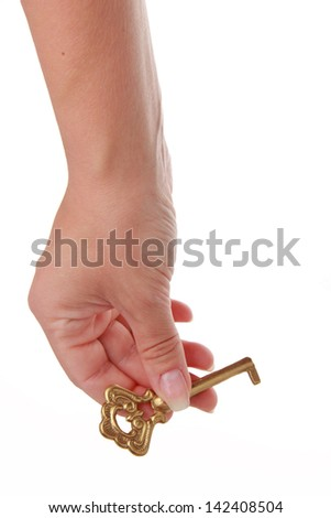 Beautiful woman hand with an old key on a white isolated background - stock photo