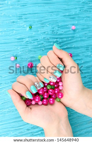 Beautiful woman hands with blue manicure holding pink beads, on color background - stock photo