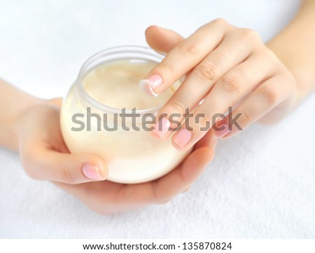 Beautiful woman hands with cream. Focus is on a finger