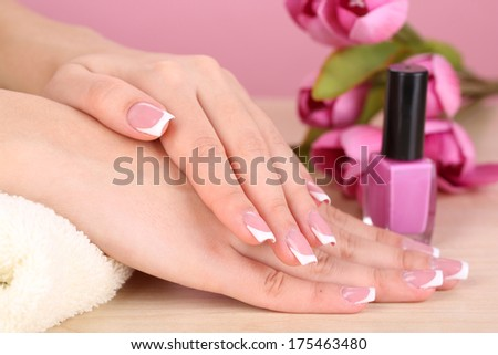 Beautiful woman hands with french manicure and flowers on table on pink background - stock photo