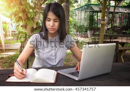 Beautiful woman hands with pen writing on leather notebook with laptop on desk table.Close up