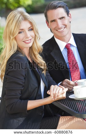 Beautiful woman & handsome man couple drinking coffee at outdoor cafe or restaurant table