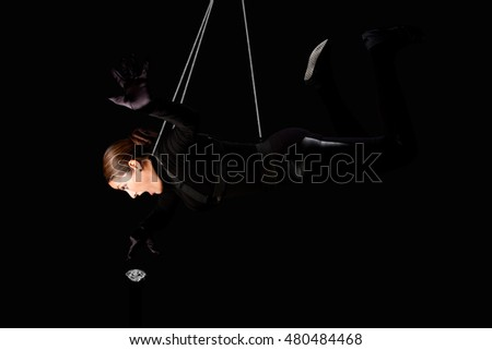 Beautiful woman hanging from wire cables stealing a diamond, jewelry heist crime concept.