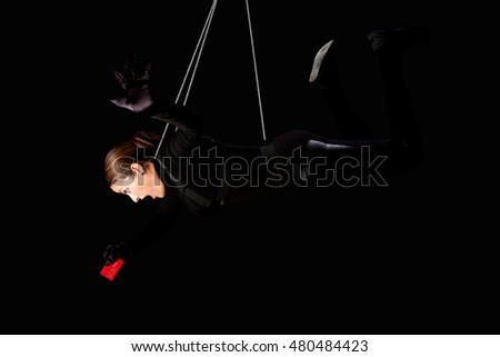 Beautiful woman hanging from wire cables stealing credit card, identity theft crime concept.