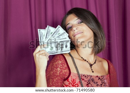Beautiful woman happy with lots of money on her hands - stock photo